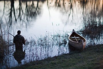 Man holding a shotgun in the water next to a canoe.
