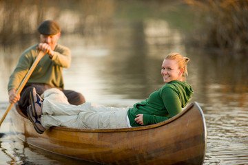 Portrait of a smiling young woman in a canoe with her boyfriend.