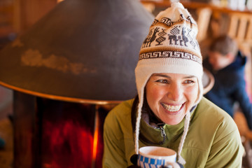 Laughing mid adult woman holding a mug of coffee while wearing a knitted hat indoors.