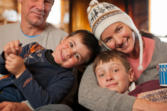 Portrait of a happy family sitting together with arms around each other.