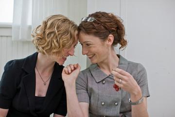 Women feeding each other grapes