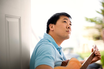 Young man playing an acoustic guitar.