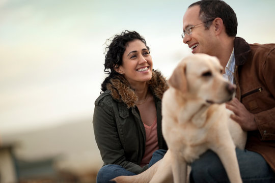 Portrait of a happy mid adult couple with their golden labrador.