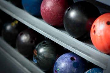 Several bowling balls lined up in a storage rack.