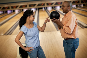 Playful mid adult woman teasing her partner at a bowling alley.