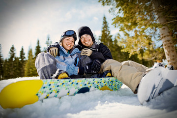 Portrait of a smiling couple wearing ski gear and sitting with their snowboards outdoors in the snow.