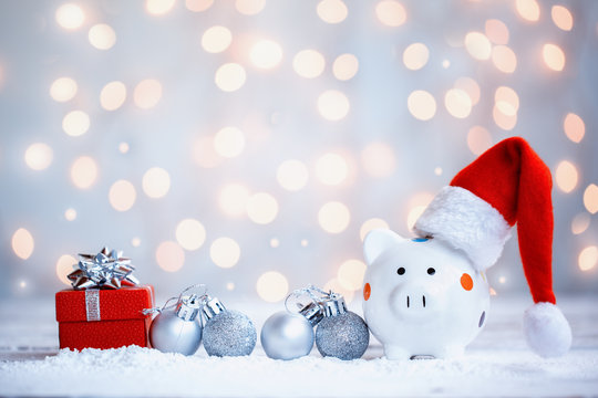Piggy bank with Santa Claus hat on holiday background. Holiday greeting card.