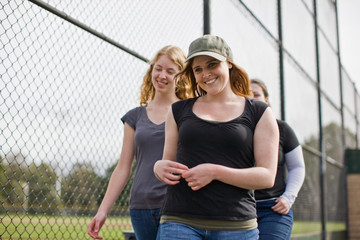 Friends walking next to sport field