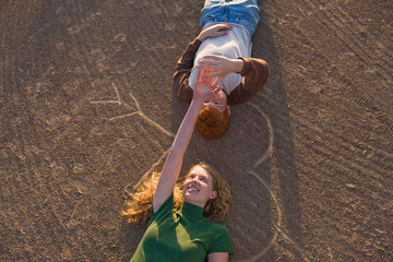 Smiling teenage couple holding hands lying on their backs on a heart shape drawn in the dirt.