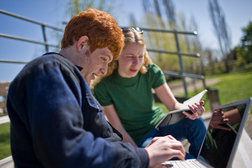 Teenage boy doing his homework outdoors on his laptop with the help of his girlfriend.