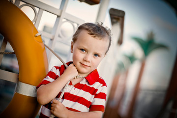 Portrait of a young boy standing on the deck of a boat.