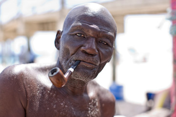Portrait of a bald senior man smoking a pipe outdoors.