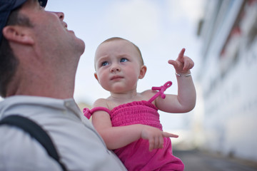 Young baby pointing and looking unsure while being held by her father.