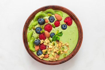 matcha tea green smoothie bowl with fresh berries, nuts, seeds and homemade granola for healthy vegan diet breakfast