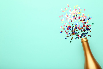 Champagne bottle with colorful confetti on mint background