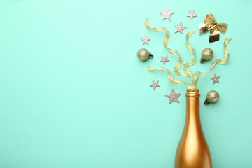 Champagne bottle with christmas decorations on mint background