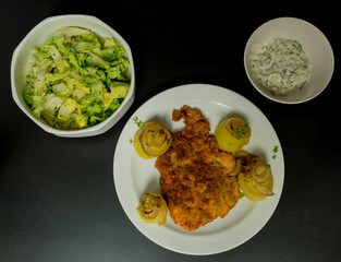 Fried wiener chicken fillet with potatoes and fried onion and two salads