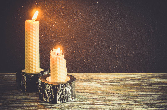 Burning wax candles on an old wooden table. Dark mystic background.