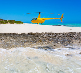 A yellow helicopter landed on idyllic empty sandy beach of remote island, azure turquoise blue lagoon in background, West Coast barrier reef, Coral sea, New Caledonia, Melanesia, South Pacific Ocean.