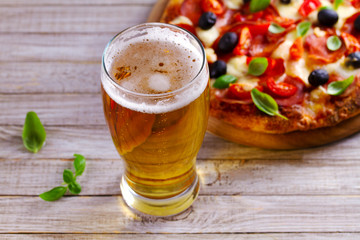 Fotobehang Bier / Cider Glass of beer and pizza on wooden table. Beer and food concept. Ale.