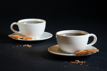 Two cups of black coffee in white cups and saucers on a black background with a cookie on each saucer.