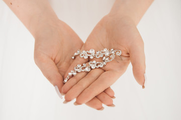 Women's wedding jewelry (earrings) in the hands of the bride, selective focus