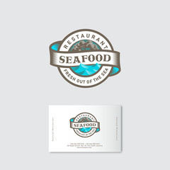 Seafood restaurant logo. Blue sea with waves, ribbon and lettering in a circle. Engraved style. Business card.