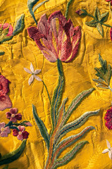 I have owned this a piece of gold coloured silk fabric embroidered with  flowers for 30 years. Authenticated as dating from before 1740 when silk was subject to high import taxes