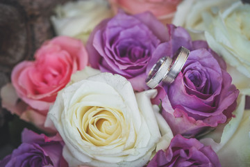 White gold wedding rings on bouquet of purple and white roses
