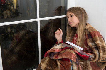 Happy new year. Small reader wrapped in plaid sit on window sill. Childrens picture book. Magic xmas spirit. Small girl enjoy reading Christmas story. Small child read book on Christmas eve