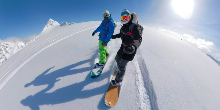 VR 360: Active young couple snowboarding together off piste on a sunny day.