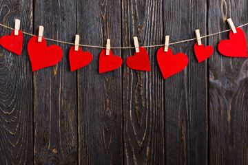 Red hearts on a rope with clothespins, on a black wooden background. Place for text, copy space.