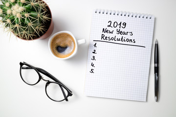 New year resolution 2019 on desk. 2019 goals list with notebook, coffee cup and glasses on white background. Goal, plan, strategy, change, idea concept. Top view