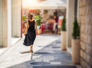 Young woman on the street of the old city in a dress on a sunny day.
