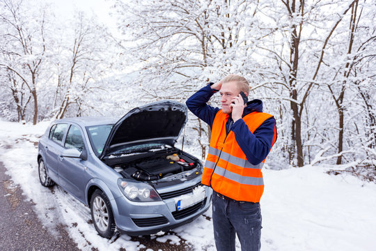 Young man calling for car service,have problem with car at winter day