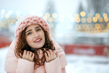 Winter portrait of cute brunette young lady wearing warm trendy outfit, walking at the Christmas fair in Kyiv. Space for text