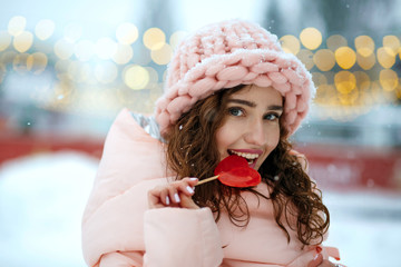 Winter portrait of flirty young lady wearing warm trendy outfit, biting tasty candy in a heart shape. Space for text