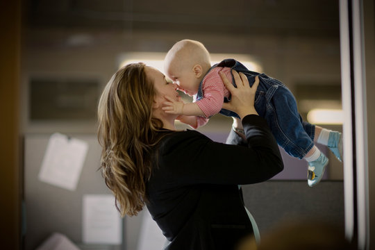 Young businesswoman holding her young baby aloft and touching noses while standing inside an office.