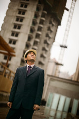 Mid-adult businessman standing in a construction site.