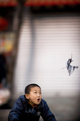 Boy following a floating piece of paper.