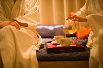 Tea being poured into cups by robe wearing people.