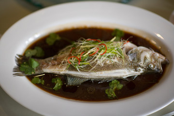 Fresh fish lying in a bowl of soup.