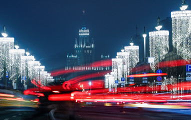 Cars pass along a street decorated with Christmas and New Year lights with a Stalin's era skyscraper in the background, in Moscow