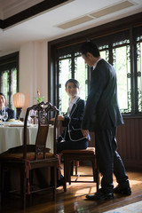 Businessman and businesswoman looking at each other inside a restaurant.