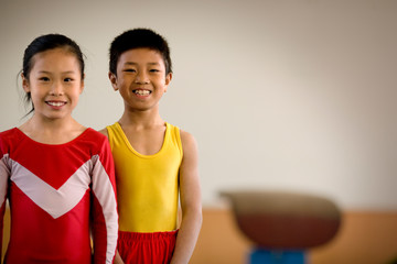 Portrait of a boy and girl standing in a gym.