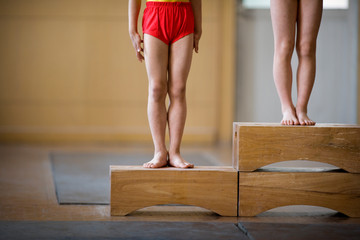 Legs of gymnasts standing on box steps.