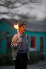 Mature adult man holding an Olympic torch in a park.