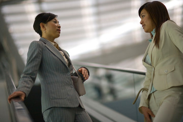 Young adult business women going down an escalator.