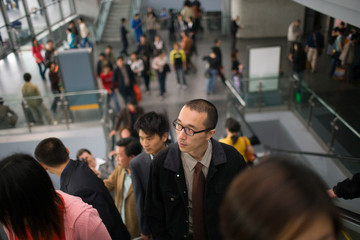 Young adult man going up an escalator with a group of people.