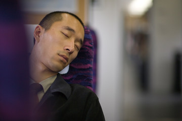 Young adult businessman sleeping on a train.